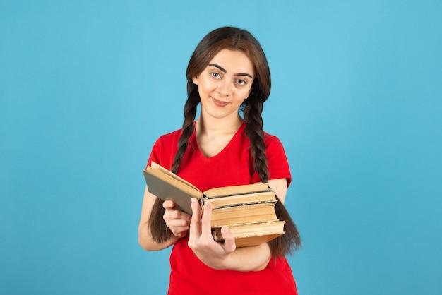 Belle étudiante en t-shirt rouge lisant attentivement un livre sur un mur bleu.