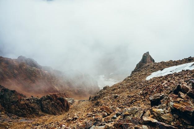 Belle falaise pointue sur le bord de la haute montagne rocheuse avec de la neige parmi les nuages bas épais. paysage alpin minimaliste atmosphérique. pierre escarpée pointue près de l'abîme dans un gros nuage. magnifiques paysages des hautes terres.