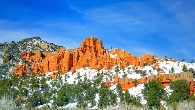 Belle falaise rocheuse entourée de collines couvertes de neige et d'arbres sous le ciel bleu clair