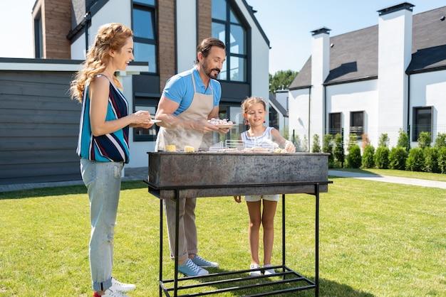 Belle famille agréable debout ensemble tout en préparant la nourriture