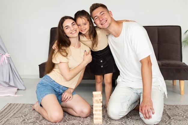 Belle famille allongée sur le sol à côté d'un jeu