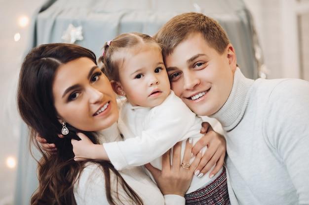 Belle famille caucasienne à noël mère et père brunette avec une fille adorable souriant à la caméra.