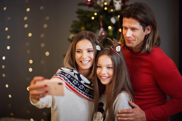 Belle famille célébrant noël à la maison et prenant le selfie