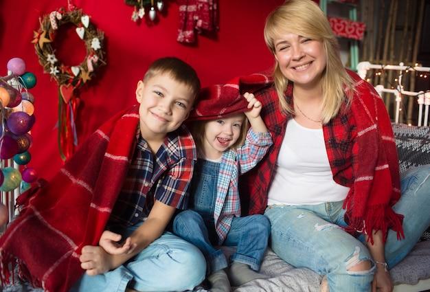Belle famille dans les vêtements du nouvel an, étreignant, s'amusant dans la maison