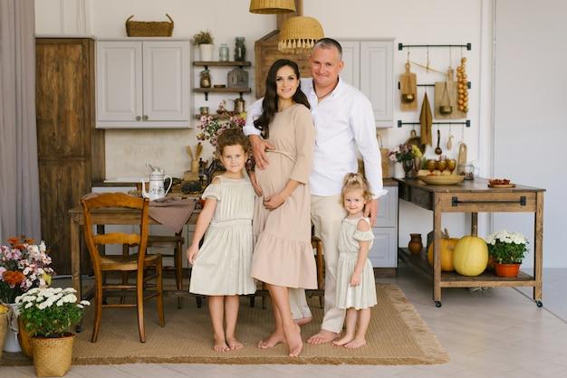 Belle famille avec deux filles souriantes dans la cuisine, maman enceinte tenant les mains sur son ventre