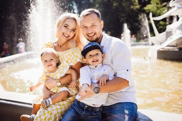 Belle famille habillée dans les mêmes vêtements se trouve sur la fontaine avec leurs enfants et des ballons jaunes