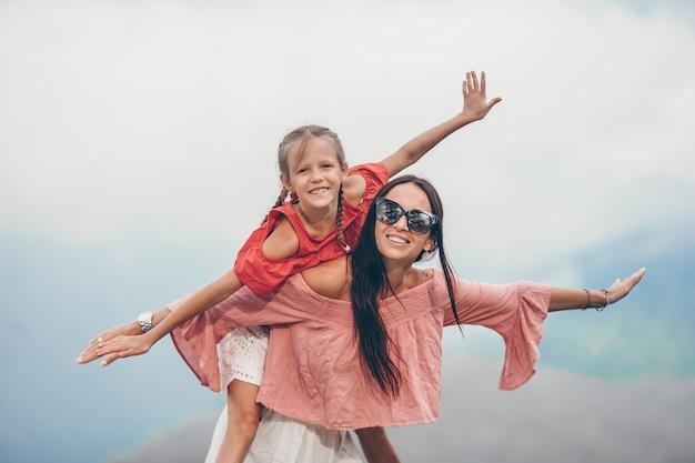 Belle famille heureuse dans les montagnes en arrière-plan du brouillard. paysage magnifique