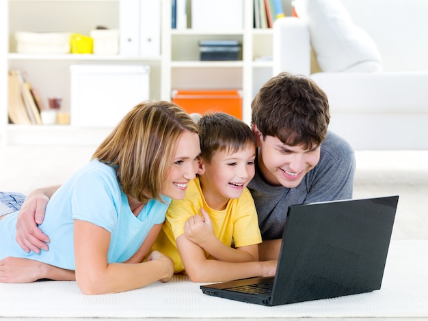 Belle famille heureuse avec enfant regardant un ordinateur portable avec un sourire joyeux - à l'intérieur