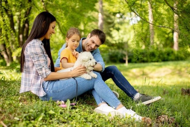 Belle famille heureuse s'amuse avec un chien bichon à l'extérieur dans le parc