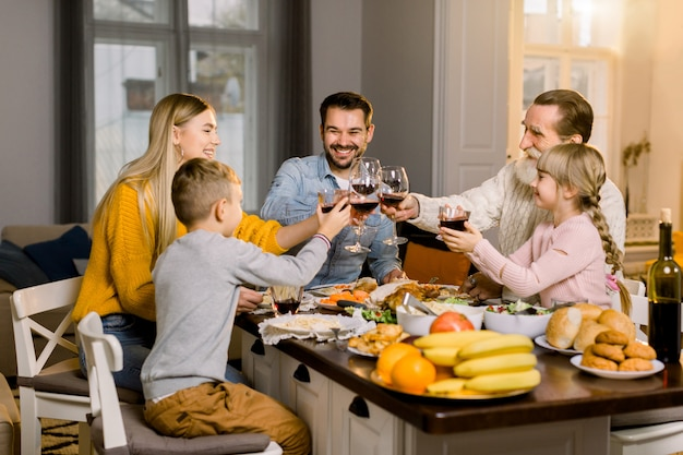 Belle famille heureuse tinter les verres de vin et de jus sur le dîner de vacances