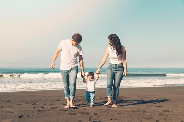 Belle famille marchant le long de la plage