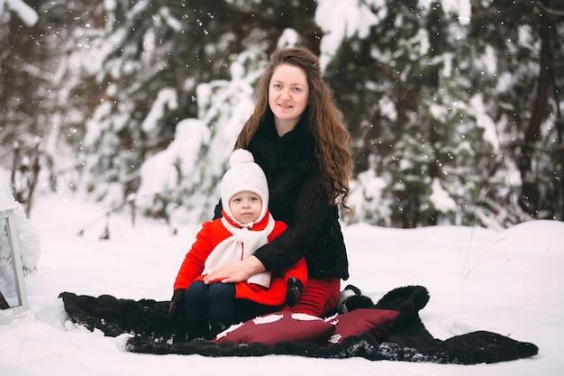 Belle famille de mère et sa petite fille appréciant la journée d'hiver enneigée en forêt