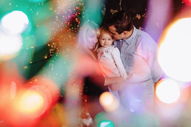 Belle famille avec petit bébé sur le fond d'un arbre de noël, célébrant le nouvel an