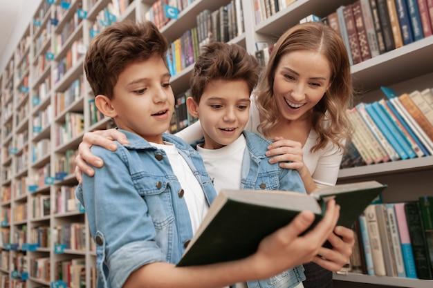 Belle famille à la recherche excitée et accablée, lisant un livre à la bibliothèque