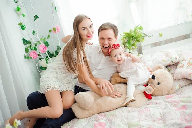 Belle famille souriant et riant, posant et se serrant dans ses bras pour une photo de famille.