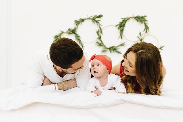 Belle famille de trois personnes sur le lit s'amusant à se regarder