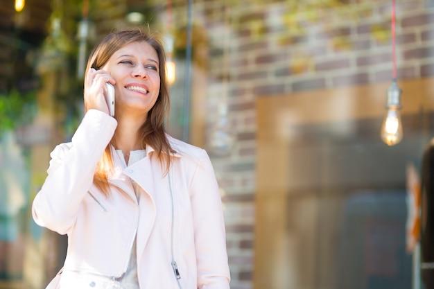 Belle femme de 30 ans marchant dans la ville par une journée ensoleillée avec un smartphone