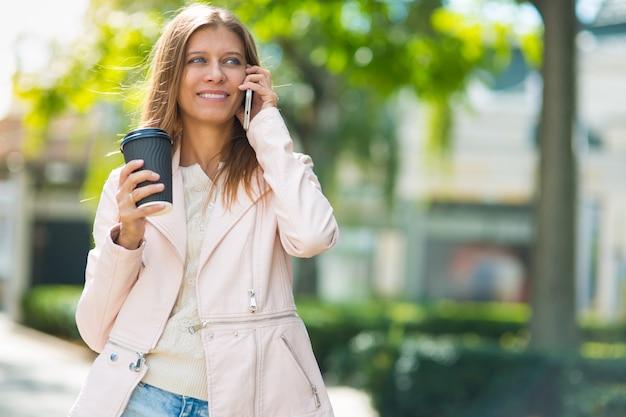 Belle femme de 30 ans marchant dans la ville par une journée ensoleillée avec une tasse de café chaud et un smartphone