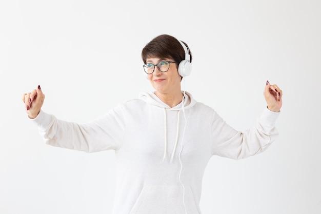 Belle femme de 40 à 50 ans à l'écoute de la musique dans un grand casque sur un mur blanc