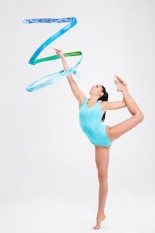 Belle femme acrobate montrer des compétences athlétiques isolé sur un mur blanc