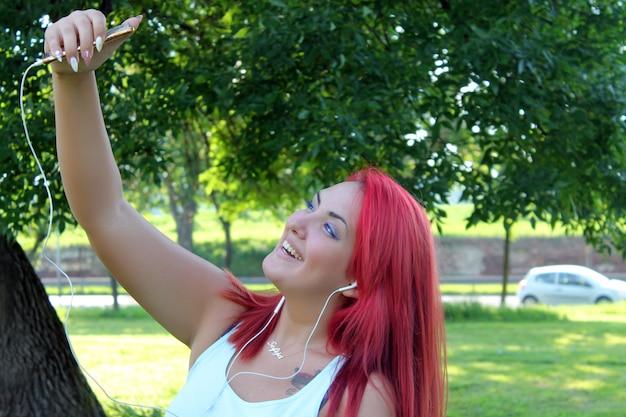 Belle femme adolescente avec des cheveux roux prenant autoportrait