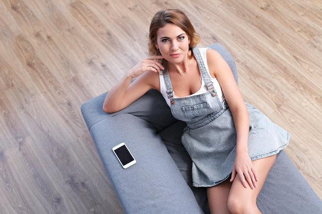 Belle femme adulte allongée sur le canapé