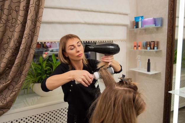 Belle femme adulte coiffeur faisant une coiffure à la clientèle blonde à l'aide d'un sèche-cheveux et d'une brosse ronde.