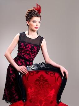 Belle femme adulte avec une coiffure de mode et un fauteuil rouge pose au studio