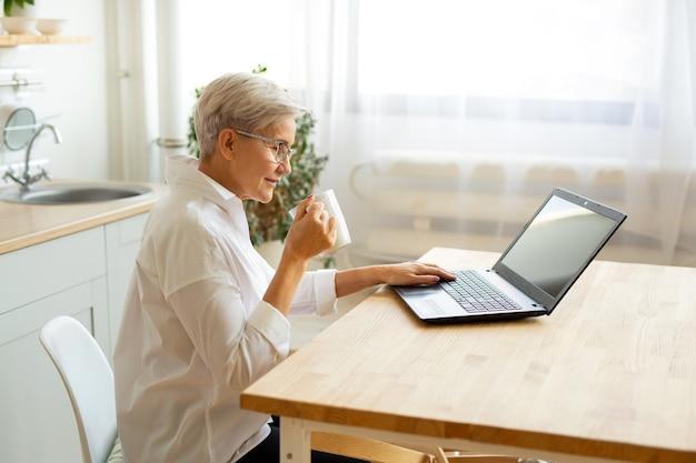 Belle femme adulte dans des verres à la table avec un ordinateur portable à la maison avec une tasse