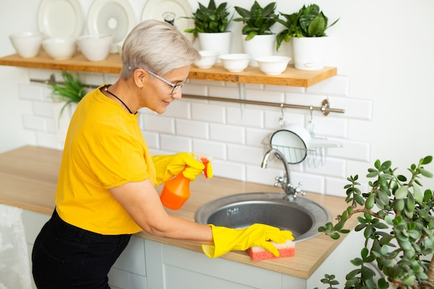 Belle femme adulte avec des lunettes dans un t-shirt jaune fait le ménage