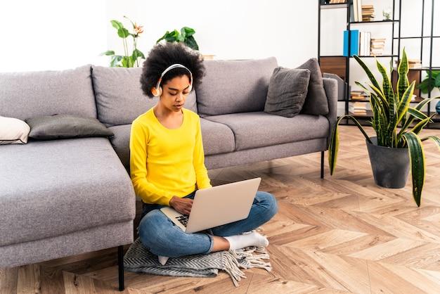 Belle femme adulte noire à la maison écoutant de la musique en ligne avec un ordinateur portable et des écouteurs - jolie fille noire travaillant à distance en ligne à la maison