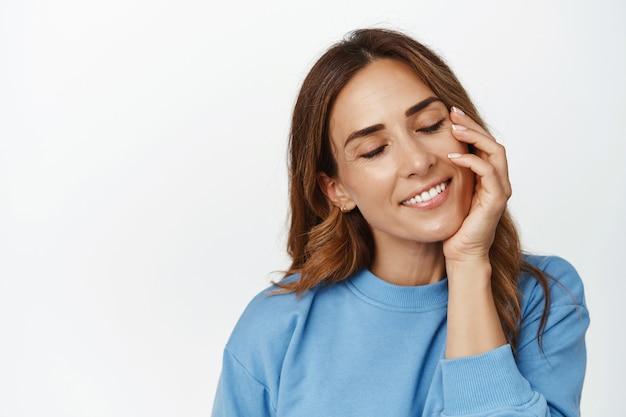 Belle femme adulte avec une peau naturelle, sans maquillage, les yeux fermés, touchant doucement le visage après les cosmétiques