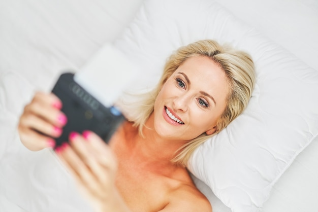 Belle femme adulte prenant une photo instantanée au lit