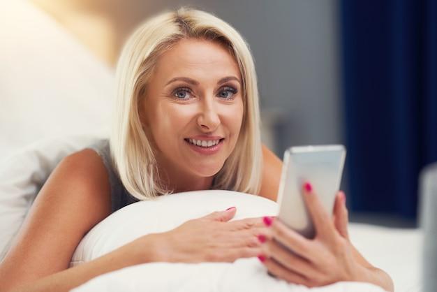 Belle femme adulte se réveillant complètement reposée et utilisant un smartphone