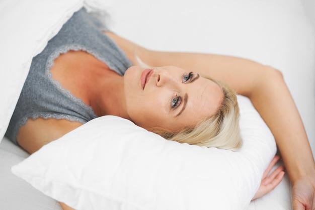 Belle femme adulte se réveillant complètement reposée.