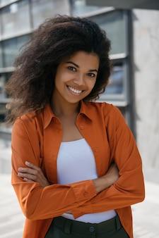 Belle femme d'affaires afro-américaine, les bras croisés, debout à l'extérieur, souriant