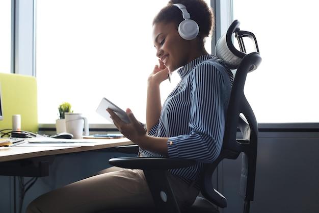 Belle femme d'affaires afro-américaine travaille à l'aide d'une tablette numérique tout en étant assise dans un bureau créatif.