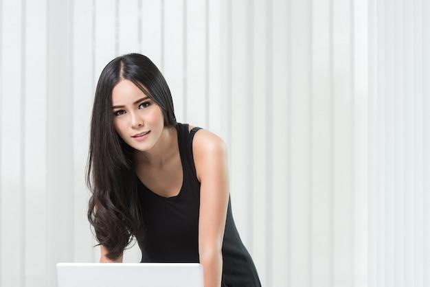 Belle femme d'affaires asiatique à l'aide d'un ordinateur portable