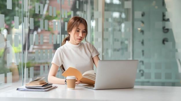 Belle femme d'affaires asiatique assise au bureau avec un ordinateur portable et un ordinateur portable.