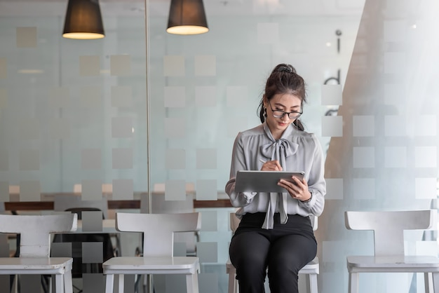 Belle femme d'affaires asiatique intelligente en prenant des notes sur la tablette dans sa chaise assise au bureau. femme d'asie en attente d'entretien d'embauche.