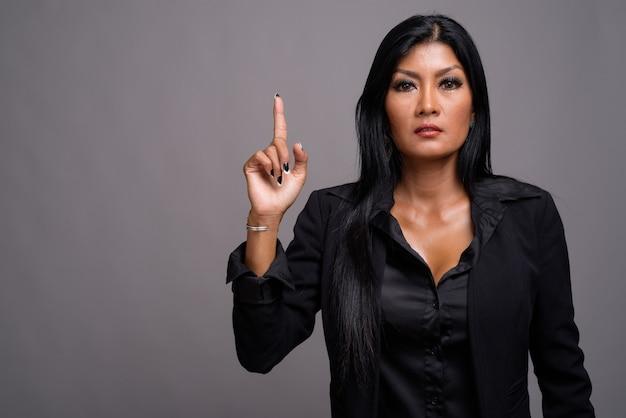 Belle femme d'affaires asiatique mature sur fond gris