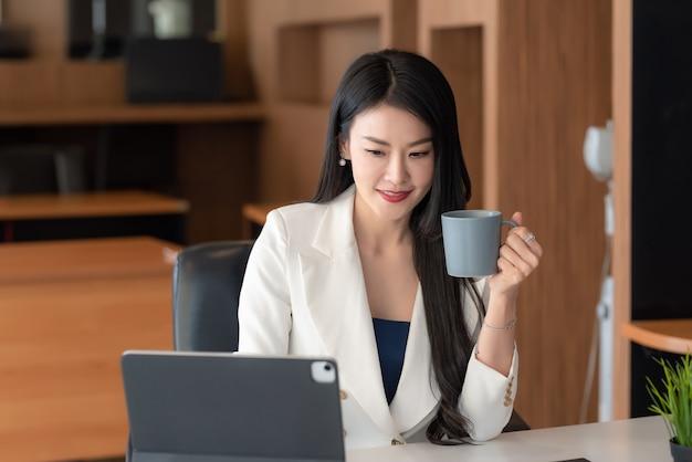 Belle femme d'affaires asiatique tenant une tasse de café travaillant à l'aide d'une tablette au bureau.