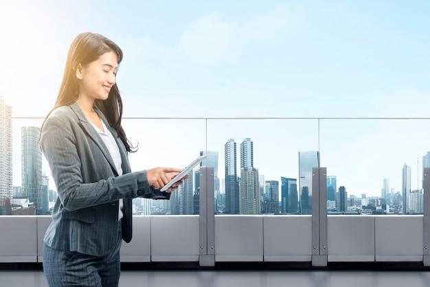 Belle femme d'affaires asiatique travaillant avec tablette numérique