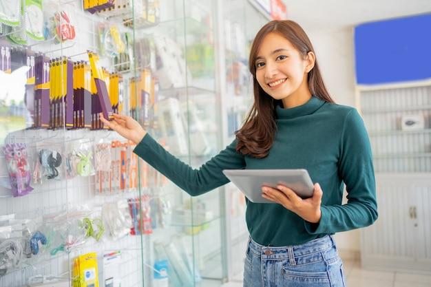 Belle femme d'affaires asiatique utilisant un tampon tout en tenant des articles de produits accessoires pour téléphones portables