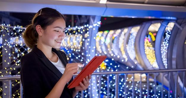 Belle femme d'affaires asiatique vérifiant le travail via une tablette via internet sur le chemin