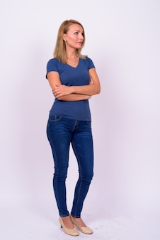 Belle femme d'affaires aux cheveux blonds portant une chemise bleue contre le mur blanc