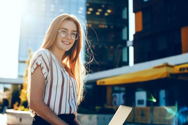 Belle femme d'affaires aux cheveux roux et taches de rousseur utilise un ordinateur portable tout en travaillant à l'extérieur dans la rue