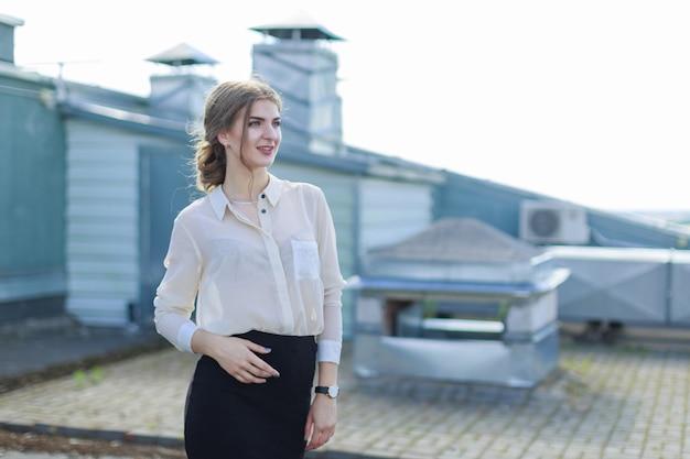 Belle femme d'affaires en blouse blanche, montre et jupe noire se tient sur le toit