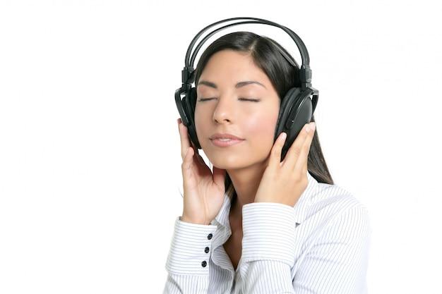 Belle femme d'affaires brune écoutant de la musique
