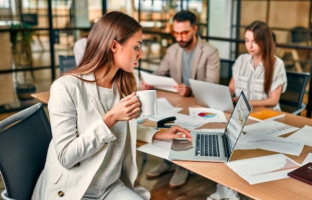 Belle femme d'affaires caucasienne avec une tasse de café ou de thé travaillant sur un ordinateur portable assis à une table de bureau avec ses collègues.